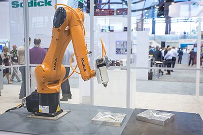 Robots enhance the productivity of machine shops and the large departments alike, because they can be programmed to do multiple tasks, from simple part articulation to complex machining.  The key is to keep them busy and the CNC can help you think ahead in that mode.  Here, the robot is polishing a mold for a quad copter drone at IMTS 2016.